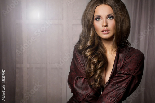 Pretty attractive  brunette woman in maroon jacket, window backg