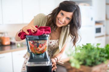 Attractive woman preparing vegetables in the blender