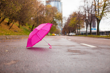 Pink children's umbrella on the wet asphalt outdoors