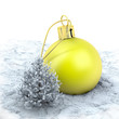 One yellow christmas ball and a small tree on a snowy ground