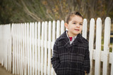 Young Mixed Race Boy Waiting For School Bus Along Fence Outside