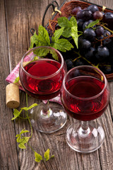 Red wine in glasses with grapes