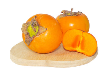 Persimmon fruit on wooden plate macro