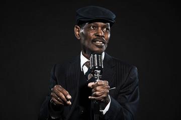 Singing retro senior afro american blues man. Wearing striped su