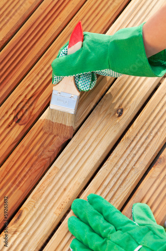 Applying protective varnish on a patio wooden floor