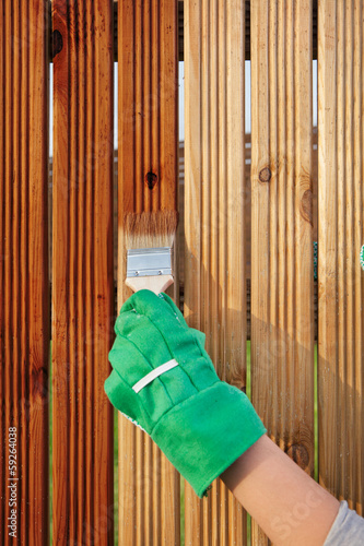 Applying protective varnish on a patio wooden fence