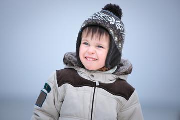 Attractive little boy having fun on winter beach