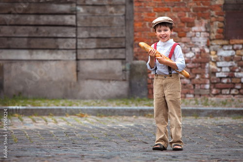 Cheerful smiling boy with baguette outdoors