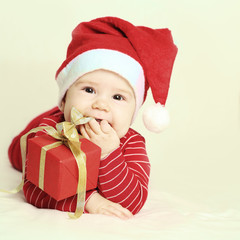 Baby in Santa hat and New Year or Christmas gift