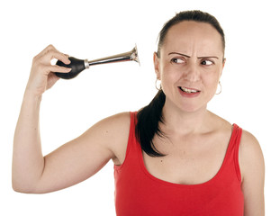 woman squeezing horn into her own ear on white background