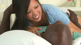 Asian and African American couple talking and laughing in bed