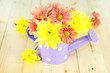 Chrysanthemum flowers in watering can on wooden table close-up