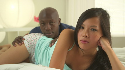African American and Asian couple lying in bed