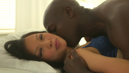 African American and Asian couple kissing each other in bed