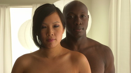 Asian woman sneaking up and covering boyfriend's eyes