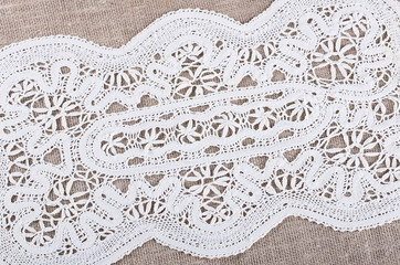 Gray textile  background with white lace napkin