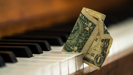 Dirty old one dollar bill stuck in a piano