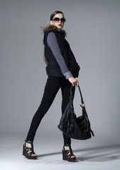 full-length young girl holding bag posing in studio