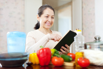 woman cooking with cookbook in the kitchen