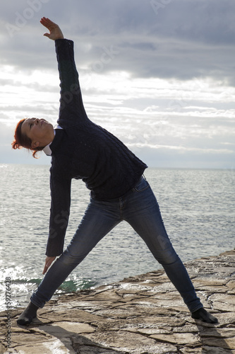 Middle aged woman at the seaside performing Yoga