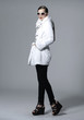 full length fashion model in white coat walking in studio
