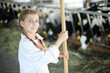 Lilttle cute girl in white with broom stands near stall