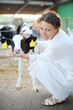 Woman in white robe caresses small calf and looks at camera
