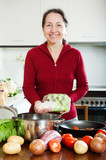 Smiling mature woman cooking soup with rice