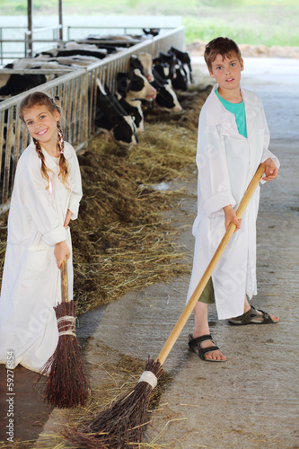 Happy brother and sister with brooms work in large farm