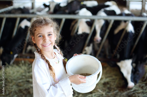 Little beautiful girl holds white bucket with food and smiles in