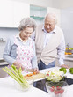 senior couple preparing meal in kitchen