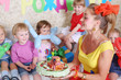 Woman holds birthday cake for little five kids at children party