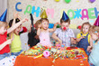 Seven happy little kids eat cake at red table at birthday party.
