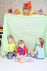 Three happy kids play with holiday host with cloth