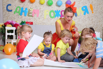 Five kids and holiday representative draw on floor