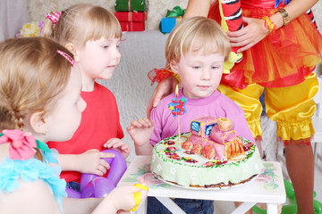 Three kids look at birthday cake with locomotive