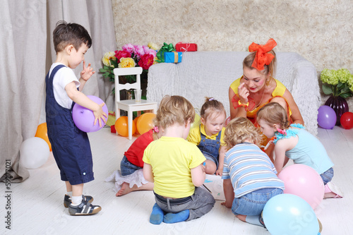 Six kids and holiday representative draw on floor