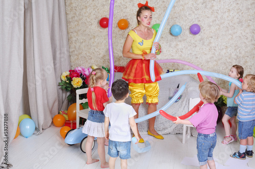 Five happy kids and facilitator play with long balloons