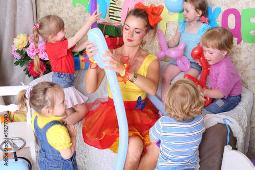 Five happy kids and facilitator make dogs of long balloons - 59277040