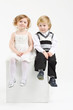 Little girl and boy sit on white big cube on white background.