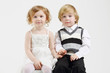 Little happy girl and boy sit on white big cube and hold hands
