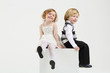 Little smiling girl and boy sit on white big cube on white