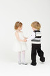 Little happy smiling girl and boy dance on white background.