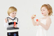 Little smiling girl and boy blow bubbles on white background