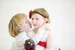 Little boy embraces and kisses pretty girl with ball-shaped lamp