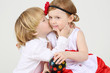 Little boy kisses pretty girl with ball-shaped lamp on white