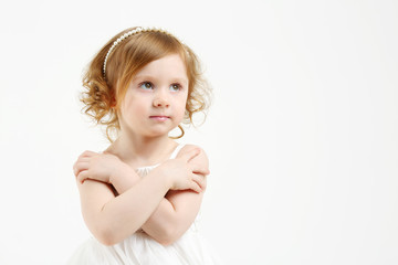 Little girl in white dress with crossed arms looks up on white