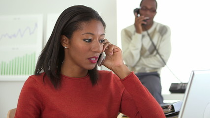 African American business woman talking on cell phone with co-wo