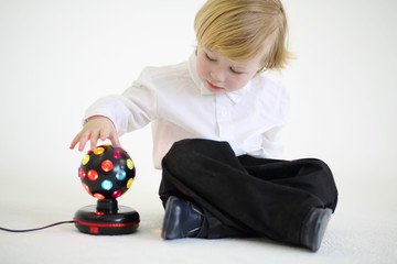 Little blond boy sits on floor with ball-shaped lamp on white