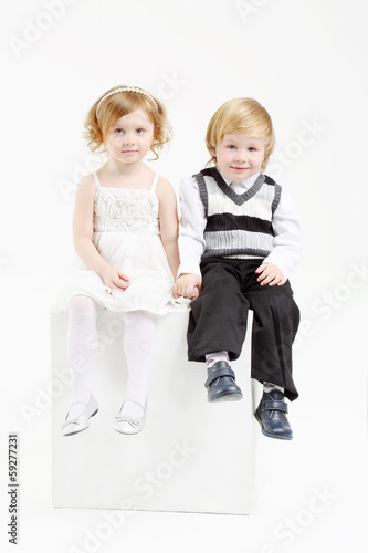 Little happy girl and boy sit on white big cube on white